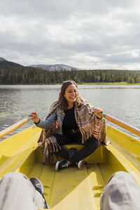 Finland, Lapland, laughing woman wearing a blanket in a rowing boat on a lake - KKAF02127