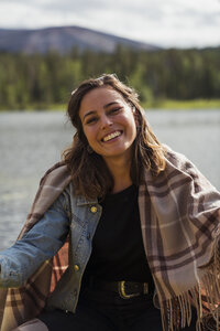Finland, Lapland, portrait of smiling young woman wearing a blanket in a boat on a lake - KKAF02130