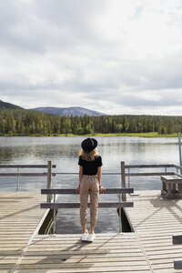 Finland, Lapland, woman wearing a hat  standing on jetty at a lake - KKAF02133