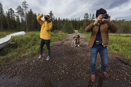 Finland, Lapland, photographers taking pictures in rural landscape - KKAF02139