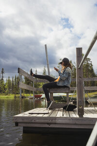 Finland, Lapland, woman sitting on jetty at a lake using cell phone - KKAF02142