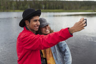 Finland, Lapland, happy couple taking a selfie at a lake - KKAF02148