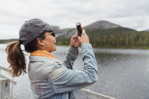 Finland, Lapland, happy woman on jetty at a lake taking a selfie - KKAF02151