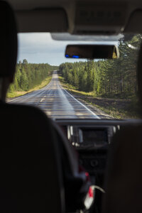 Finland, Lapland, interior view of man driving car in rural landscape - KKAF02160