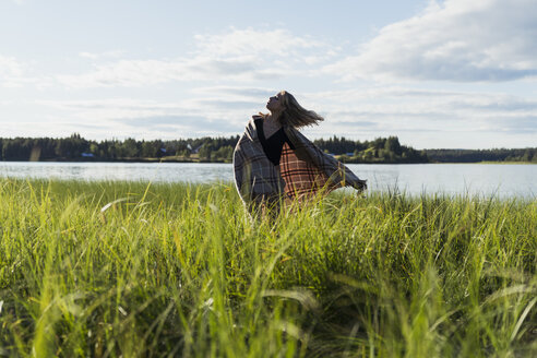 Finland, Lapland, woman with a blanket at the lakeside - KKAF02166