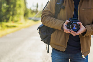 Finland, Lapland, close-up of man holding camera on country road - KKAF02169