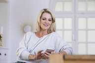 Portrait of smiling blond mature woman using smartphone at home - FMKF05297