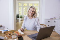 Portrait of smiling blond mature woman at home office having pizza - FMKF05306