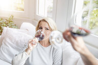 Portrait of blond mature woman drinking red wine with her partner at home - FMKF05312