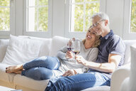 Mature couple relaxing on the couch with red wine having fun - FMKF05315