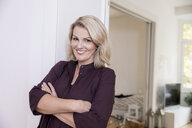 Portrait of smiling blond mature woman at home - FMKF05318