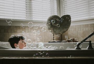 Boy looking at bubbles while taking bath in bathtub - CAVF48997