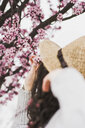 Close-up of young woman holding cherry blossoms on branch at park - CAVF49006