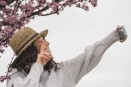 Smiling young woman gesturing peace sign while taking selfie with smart phone by cherry tree at park - CAVF49009