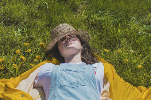 High angle view of carefree young woman with hat lying on grassy field at park - CAVF49015