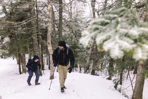 Full length of friends with hiking poles exploring forest during winter - CAVF49021
