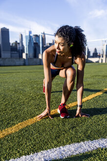 Female athlete looking away while exercising on grassy field against sky - CAVF49042