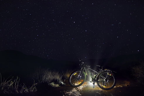 Mountain bike with illuminated light against star field at desert during night - CAVF49090