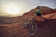 Full length of hiker by mountain bike sitting on rocks at desert during sunset - CAVF49093