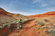 Blurred motion of hiker mountain biking at desert against sky - CAVF49099
