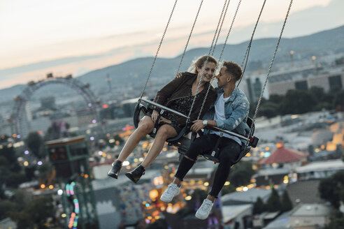 Young couple in love, riding chairoplane on a fairground - LHPF00089