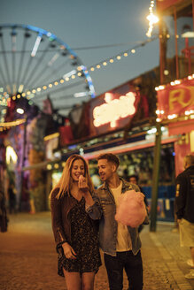 Romantic couple at a funfair eating candy floss - LHPF00107