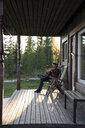 Young man sitting on veranda of a wood house, playing the ukulele - KKAF02173