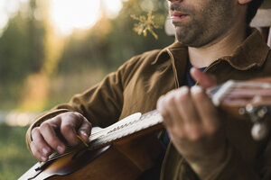 Close-up of young man, plaing the ukulele - KKAF02179