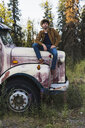 Cool young man sitting on a broken truck - KKAF02182
