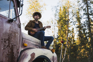 Young amn sitting on a broken truck, playing the ukulele - KKAF02185