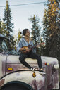 Young woman sitting on a broken truck, playing the ukulele - KKAF02191
