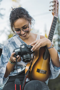 Smiling woman holding ukulele,  checking pictures on camere - KKAF02194