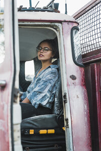 Young woman sitting in cabin of a broken vintage truck - KKAF02197