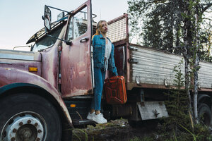 Young woman posing at a broken vintage truck, holding petrol can - KKAF02203