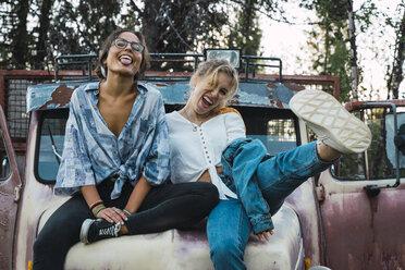 Friends sitting on a broken truck, having fun - KKAF02206