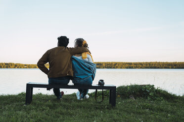 Young couple sitting on a bench, looking at the lake - KKAF02212