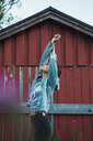 Portrait of a young woman stretching in front of a red wood hut - KKAF02218