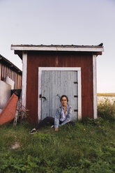 Portrait of a young woman sitting in grass in front of a wooden shack - KKAF02221