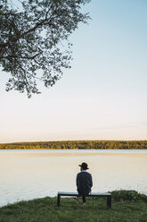 Young man sitting on a bench, looking at the lake - KKAF02227