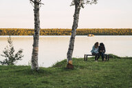 Young couple sitting on a bench near lake, checking pictures on a camera - KKAF02230