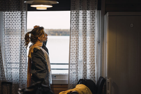 Portrait of a young woman standing in a room with a window - KKAF02233