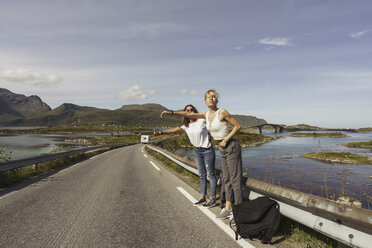 Young women hitchhiking on an empty road, Lapland, Norway - KKAF02242