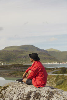 Young man sitting on rock in Vesteralen island, Lapland, Norway - KKAF02251