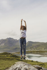 Young woman jumping on a rock, Lapland, Norway - KKAF02254