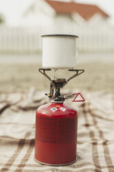 Cup of coffee boiling on a camping stove - KKAF02260