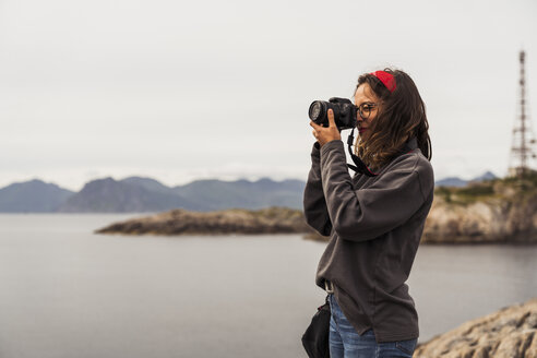 Young woman taking pictures of a lake in Vesteralen Island, Lapland, Norway - KKAF02266
