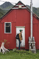 Young man standing in front of corrugated iron shack - KKAF02269