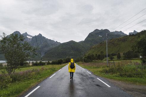 Norway, Lapland, Vesteralen Islands, Young man walking on empty road, rear view - KKAF02272