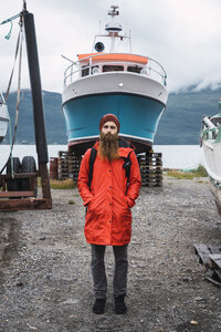 Young man standing in front of a ship, wearing rain clothes, Lapland, Norway - KKAF02281