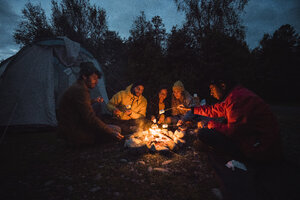 Group of friends sitting at a campfire, roasting marshmallows - KKAF02293